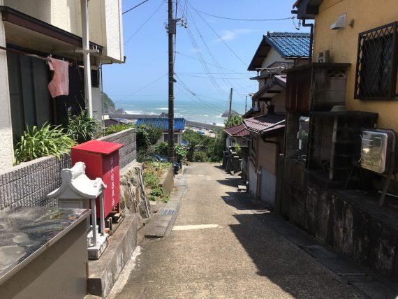 狭い坂道から見える海