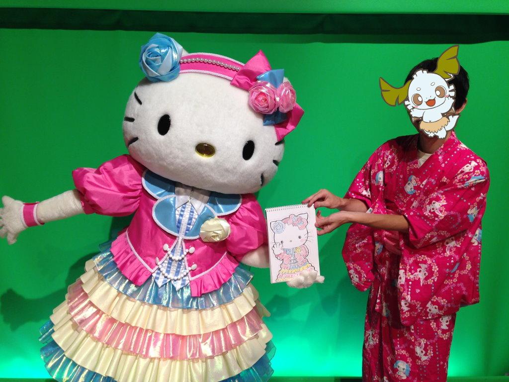 26周年記念の衣装のキティちゃんが描かれた絵を持つ手を広げるキティちゃんとオレ