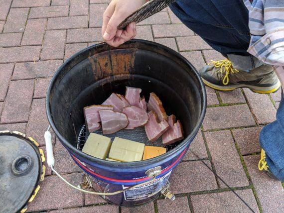 燻製器の中にお肉とチーズを入れるよ
